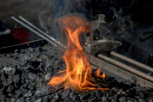 A burning forge with flames is pictured. Many serious burn injuries occur at work.